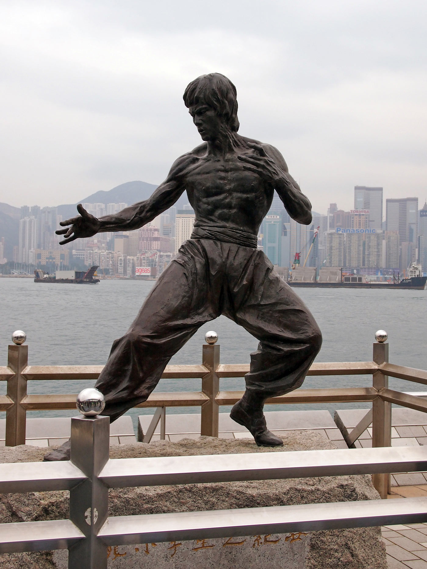 Bruce Lee in der Avenue of Stars mit der Skyline von Hong Kong