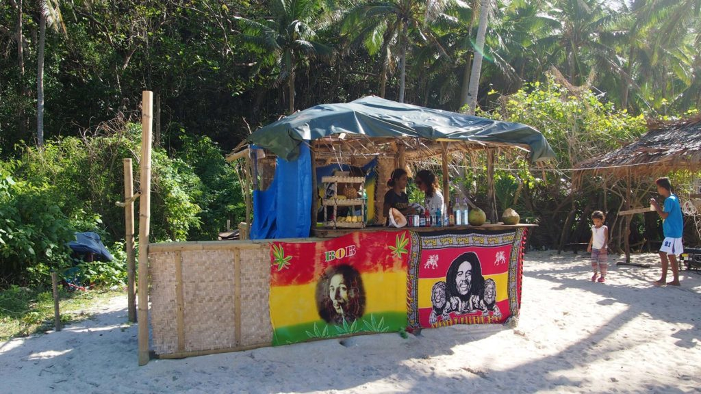 Small beach bar with Bob Marley flags on Puka Beach