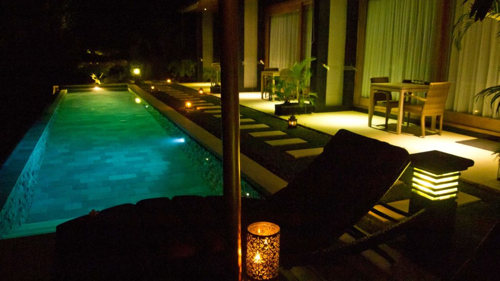 The outdoor and pool area of The Puncak at night