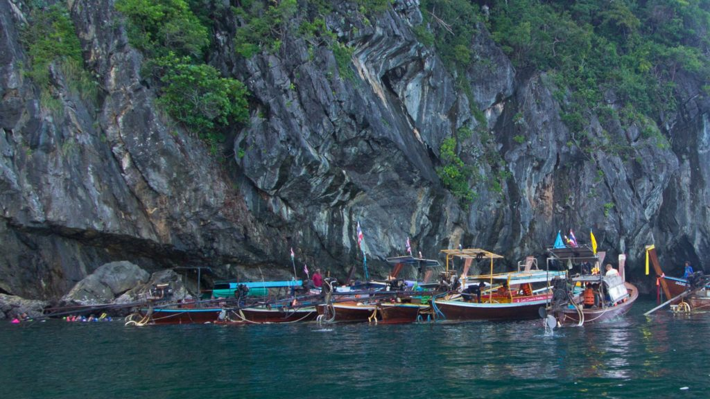Many boats in front of the entrance to the Emerald Cave on Koh Mook