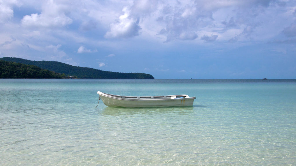A lonely boat in the crystal clear water of the Saracen Bay, Koh Rong Samloem