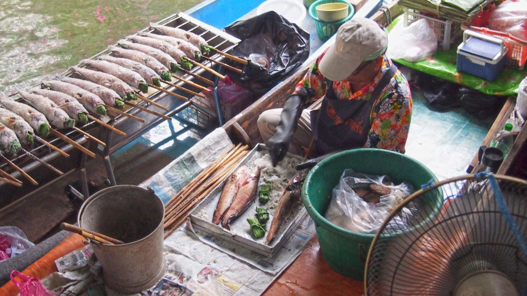 Some vendor prepares fish on a boat at the Taling Chan Floating Market in Bangkok