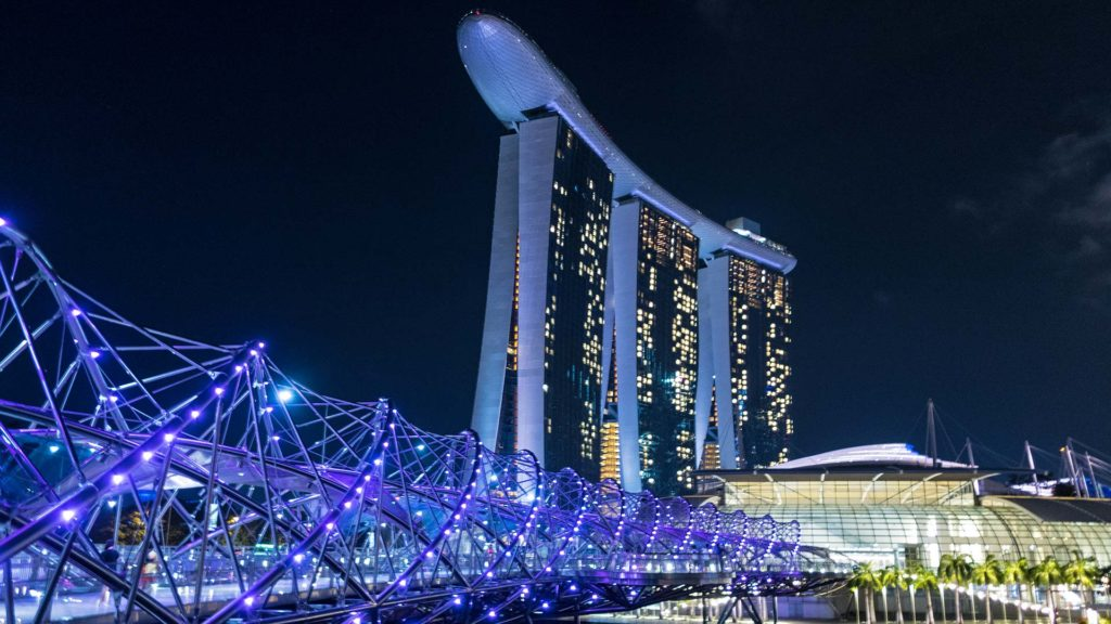 The Helix Bridge at night, in the background the Marina Bay Sands