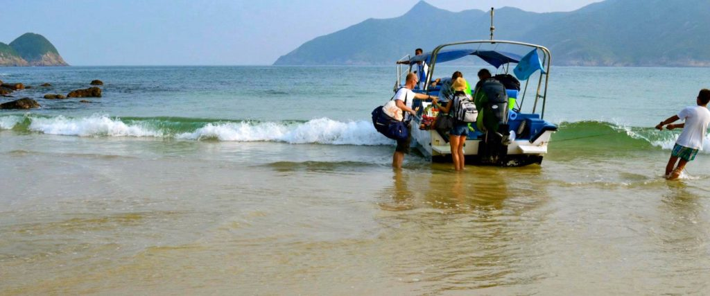 Boot mit Touristen legt am Sai Wan Beach in Hong Kong an
