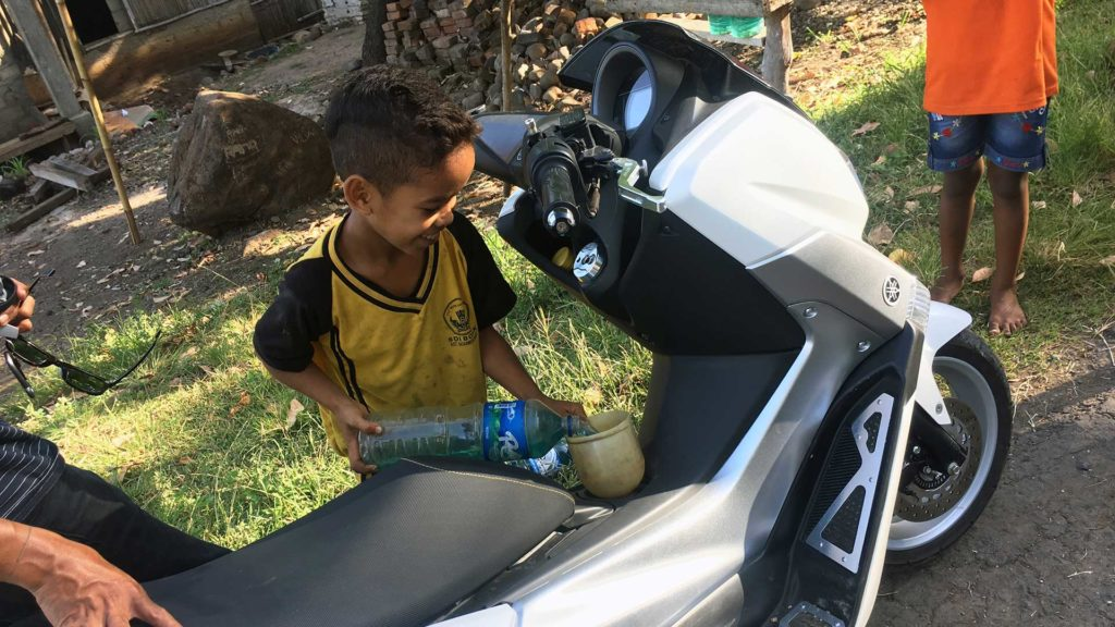 Child refueling the scooter in Flores, Indonesia