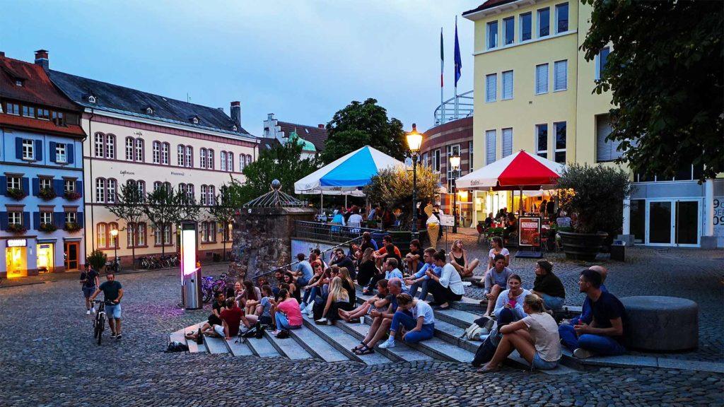 Menschen am Abend auf dem Augustinerplatz in Freiburg