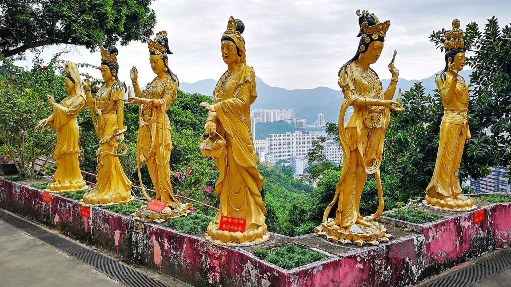 Buddhist statues with a view of the Hong Kong skyline